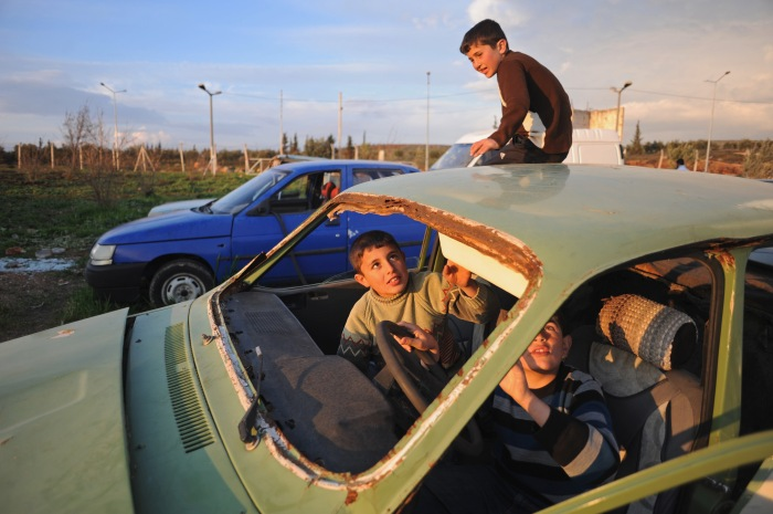 "Syrian children play in a junkyard of old, abandoned and destroyed vehicles at the entrance to the Reyhanli tent city in Reyhanli, Turkey on February 26, 2012.  As the year old rebellion against the rule of Bashar Al-Assad continues just across the border in Syria, Turkey has seen a continued influx of refugees from the Syrian conflict but has not granted them refugee status and instead considers them to be ""guests"" of Turkey."