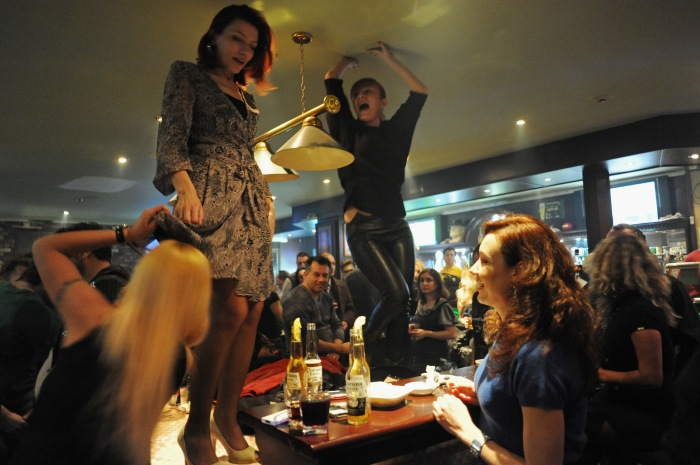 Women dance on the tables at Shakespeare bar in Baku, Azerbaijan on March 18, 2012.