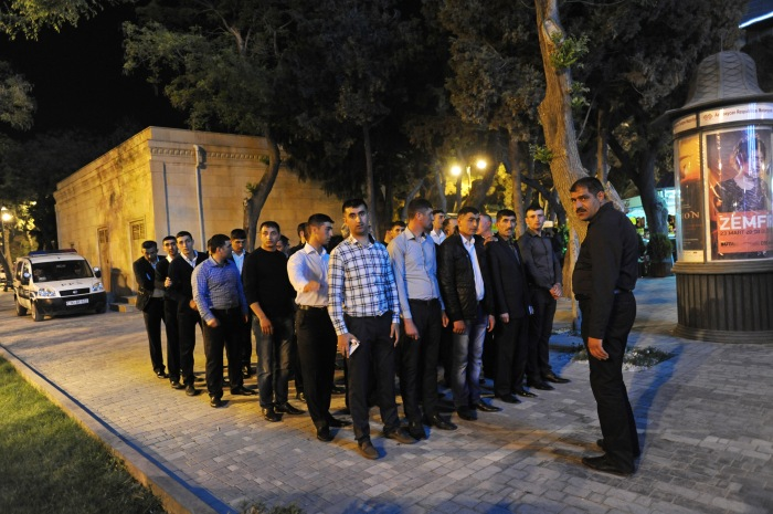 Plain clothes police officers line up in formation after managing security during the Eurovision Fan Club concert on the Bulvar seaside promenade in Baku, Azerbaijan on April 29, 2012.