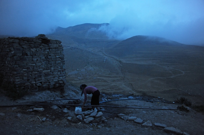 A woman fetches fresh water from a pipe perched high in the mountains in Xenaliq, Azerbaijan on August 19, 2012.  Xenaliq is one of the oldest continuously inhabited mountain villages in Eurasia and the last village on the road before the Azerbaijani border with the Russian North Caucasus territory of Dagestan.