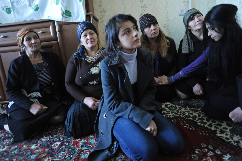 (Center) Gamar Tagili, 15, the daughter of slain writer Rafiq Tagi, sits with her mother (behind and to the left), the widow Maila Tagiyeva, 47, and Tagi's two sisters (behind and to the two to the right) Yeguna and Durdana, during the third-day memorial in his apartment surrounded in Baku, Azerbaijan on November 26, 2011.  A critic until his very last article of Iran's theocratic regime with a fatwa ordered against his life by the late Iranian Ayatollah Fazil Lankarani and others in 2006, Tagi was once imprisoned for eight months in 2007 by Baku's secular ruling Aliyev family and stabbed repeatedly by a silent, unknown assailant while returning home the evening of November 19 and died of complications after having his spleen removed several days later; after initial silence, Azerbaijan authorities have opened an investigation and many of Azerbaijan's intelligentsia point their finger at Iran despite an official denial from the Iranian Embassy in Baku.